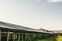 Lång frilufts- ladugård med ett kors på dess topp fotografering för bildbyråer