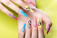Lång härlig manikyr i pop-konst stil på kvinnliga fingrar Spikar design Närbild Royaltyfri Foto