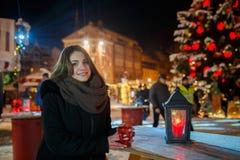 Lång hårflicka på europeisk julmarknad Ung kvinna som tycker om vintersemesterperiod Suddig ljusbakgrund, skymning Kuper wi royaltyfria bilder