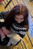 Lång haired flicka på en lantgård som kramar ett nyfött lamm arkivbilder