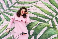 Lång haired lockig brunettkvinna i rosa klänning och rosa exponeringsglas arkivbild