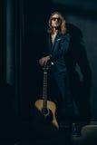 Lång haired man i solglasögon och den stilfulla dräkten som poserar med den akustiska gitarren Royaltyfri Fotografi