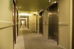 Lång hotellkorridor med dörrar och hissen Arkivbild