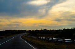 Lång huvudväg på solnedgången Royaltyfri Bild