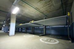 Lång inomhus två-nivå parkering med electrolifts Fotografering för Bildbyråer