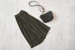 Lång kaki- kjol med handväskan på träbakgrund innegrej royaltyfri foto