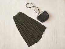 Lång kaki- kjol med handväskan på träbakgrund innegrej royaltyfri fotografi