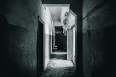 Lång korridor med dörrar i spökad och förstörd övergiven industribyggnad royaltyfri bild
