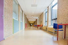 Lång korridor med möblemang i skolabyggnad Arkivfoto