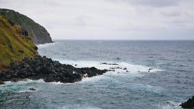 Lång kustlinje längs en stenig lös kust med ett turbulent hav arkivfilmer
