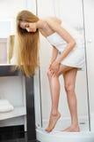 lång kvinna för ben Den härliga kvinnan att bry sig om ben efter dusch Arkivfoto