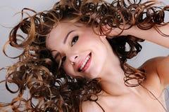 lång le kvinna för gladlynt lockiga hår royaltyfria foton