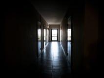 Lång mörk korridor med dörrar till lägenheterna royaltyfri fotografi