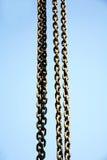 Lång metall kedjar fast att hänga vertikalt mot blå himmel Arkivfoto
