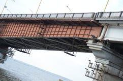 Lång metallbro över floden i staden Gammal konstruktion arkivfoto