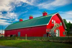 Lång röd ladugård med det gröna taket Royaltyfria Foton