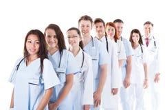 Lång rad av att le doktorer och sjuksköterskor arkivbild