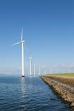 Lång rad av kustvindturbiner i det holländska havet Arkivfoton