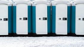 Lång rad av mobila toaletter utanför på den snöig jordningen Bio toaletter utomhus royaltyfri foto