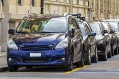 Lång rad av nya skinande dyra bilar som parkeras längs den rena tomma stadsgatan på stor stenbyggnad på den ljusa soliga sommar e arkivfoto