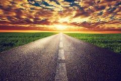 Lång rak väg, väg in mot solnedgångsolen Royaltyfri Fotografi