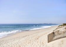 Lång sandig strand med vindskydd på stranden arkivbilder