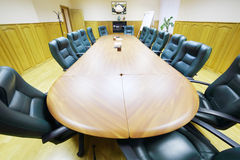 Lång tabell, fåtöljer i rum för affärsmöten Royaltyfri Bild