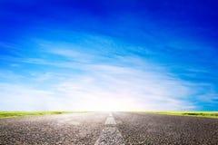 Lång tom asfaltväg, huvudväg in mot solen Fotografering för Bildbyråer