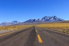 Lång väg med gula linjer och berg arkivbilder