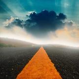 Lång väg och dramatisk himmel med solstråle Arkivbilder