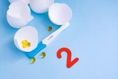 Lång-väntad på havandeskap efter mislyckad IVF Positiva graviditetstest, piller, äggskal och två royaltyfri foto