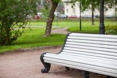Lång vit målade träbänken i stads- sommar parkerar, inget arkivbilder