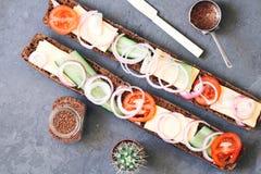 Lång vresig bagett varm nytt bakade råg bröd med ost, gurkan och tomater med lökar på ett lantligt arkivfoton