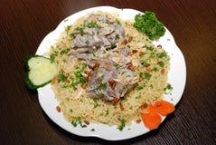 Långa basmati ris med grönsaker och kött som kryddas med, sörjer muttrar och kryddor arkivfoto