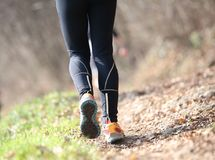 Långa ben av idrottsman nen med svart damasker under landet Royaltyfri Foto