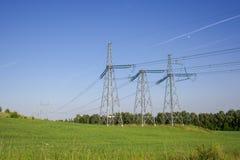 Långa elektriska linjer, torn och höga spänningslinjer i ett fält i sommar arkivfoto