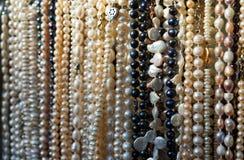 Långa pärlor av naturliga flodpärlor i en gata shoppar arkivbilder