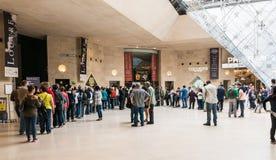Långa rader väntar för att gå till och med säkerhet på den underjordiska Louvre Arkivfoton