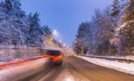 Långa slingor av billjus på vägen som täckas i snö på aftonen Arkivbild