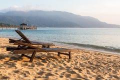 Långa stolar på en strand i Pulau Tioman, Malaysia Fotografering för Bildbyråer