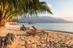 Långa stolar på en strand i Pulau Tioman, Malaysia Arkivbild