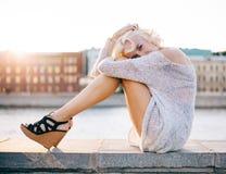 Långbent flicka för mode i härliga hög-heeled skor som sitter på stranden på sommarsolnedgången arkivfoton