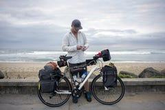Långdistans- cyklist med cykeln vid havet arkivfoton