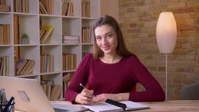 Långhårig affärskvinna för ung brunett som i regeringsställning arbetar med bärbar dator- och anteckningsbokleenden in i kamera lager videofilmer