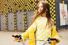 Långhårig blond flicka i en gul tröja och ett gult omslag arkivfoton