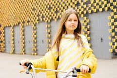 Långhårig blond flicka i en gul tröja och ett gult omslag arkivbilder