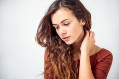 Långhårig brunett på en vit bakgrund Royaltyfri Fotografi