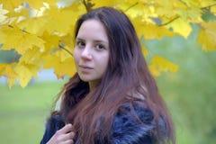 Långhårig brunetttonåring med ett blått omslag fotografering för bildbyråer