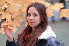 Långhårig brunetttonåring med ett blått omslag royaltyfri fotografi