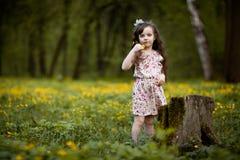 Långhårig flicka med gula blommor Arkivbilder